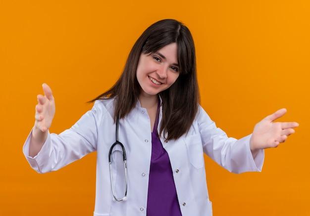 De glimlachende jonge vrouwelijke arts in medisch kleed met stethoscoop houdt beide handen open op geïsoleerde oranje achtergrond met exemplaarruimte