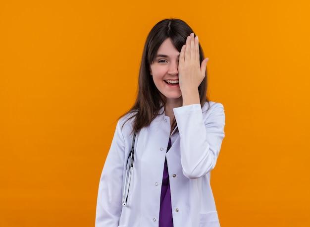De glimlachende jonge vrouwelijke arts in medisch kleed met stethoscoop sluit haar oog met hand op geïsoleerde oranje achtergrond met exemplaarruimte