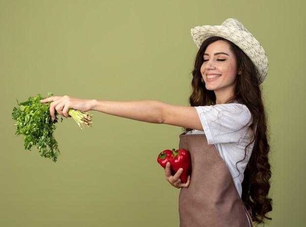 De glimlachende jonge vrouwelijke tuinman in uniform die het tuinieren hoed draagt houdt koriander en rode paprika's die op olijfgroene muur worden geïsoleerd