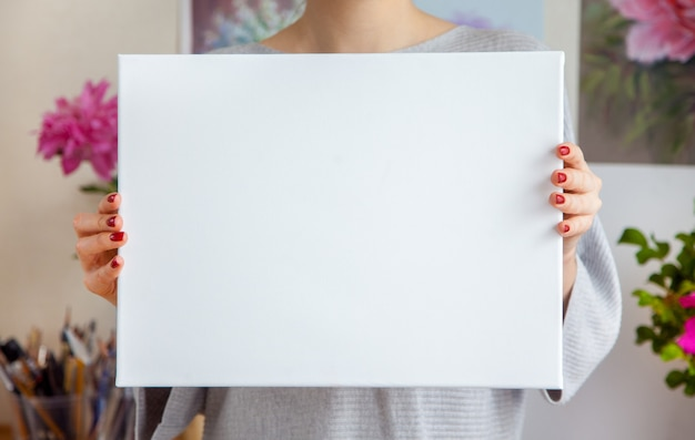 De glimlachende jonge vrouwenkunstenaar houdt een leeg wit canvas in haar handen tegen de achtergrond van een gezellige werkplek met schilderijen aan de muur en gereedschap. advertentie ruimte