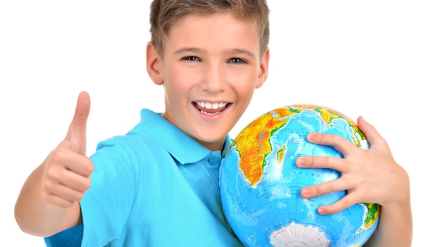 De glimlachende jongen in toevallige holdingsbol met duimen ondertekent omhoog - op wit wordt geïsoleerd