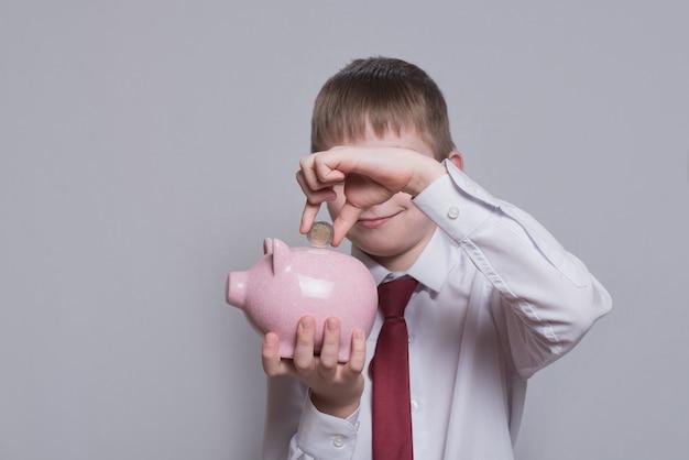 De glimlachende jongen legt een muntstuk in een roze spaarvarken. bedrijf. licht