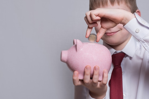 De glimlachende jongen legt een muntstuk in een roze spaarvarken. bedrijfsconcept.