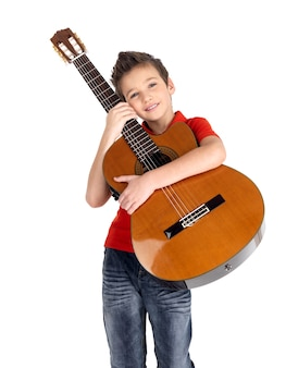 De glimlachende kaukasische jongen houdt de akoestische gitaar die op wit wordt geïsoleerd