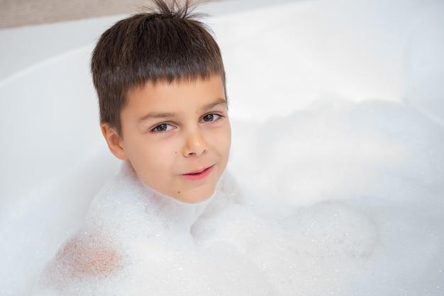 De glimlachende kaukasische jongen neemt een bad met schuim. jeugd, neem een bad, hygiënisch thema.