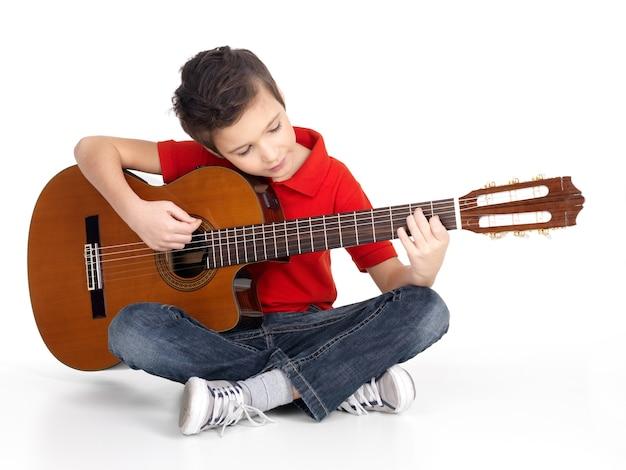 De glimlachende kaukasische jongen speelt de akoestische die gitaar - op witte achtergrond wordt geïsoleerd