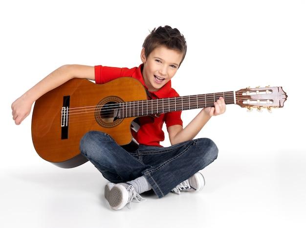 De glimlachende kaukasische jongen speelt op akoestische gitaar die op wit wordt geïsoleerd
