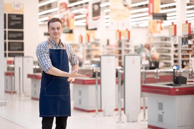 De glimlachende kaukasische verkoper nodigt uit om met een gebaar op te slaan