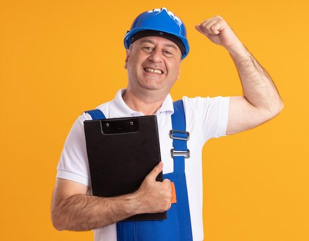 De glimlachende kaukasische volwassen bouwersmens in uniform houdt klembord en werpt vuist omhoog op sinaasappel