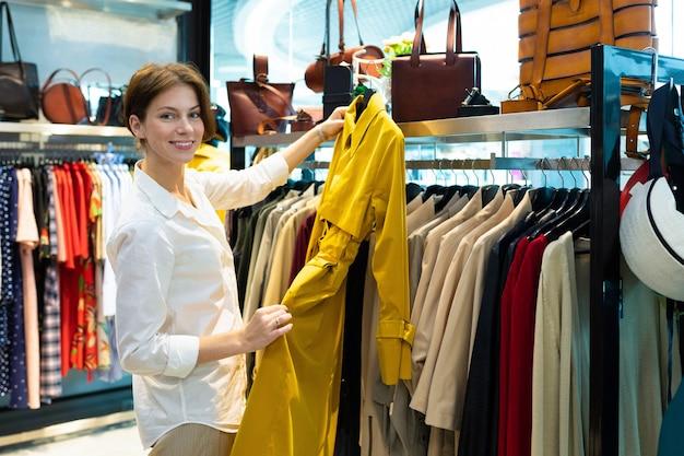 De glimlachende kaukasische vrouw houdt de gele laag in haar winkelcomplex indient