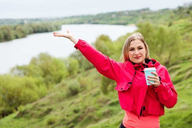 De glimlachende kaukasische vrouw houdt kop van drank in één hand en raspt een andere hand die mooi aardlandschap toont