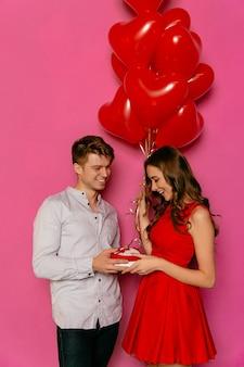 De glimlachende kerel geeft doos met heden, rode ballons in vorm van hart voor zijn mooi meisje