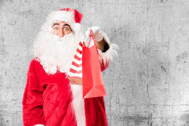 De glimlachende kerstman met boodschappentassen