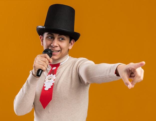 De glimlachende kijkende jonge kerel die hoed draagt met kerstmisband spreekt op microfoonpunten aan kant die op gele muur worden geïsoleerd