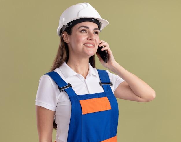 De glimlachende kijkende kant jonge bouwersvrouw in uniform spreekt over telefoon die op olijfgroene muur wordt geïsoleerd