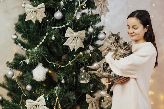 De glimlachende kittens van de meisjesholding dichtbij kerstboom.