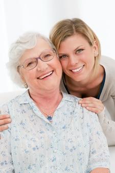 De glimlachende kleindochter omhelst thuis haar grootmoeder