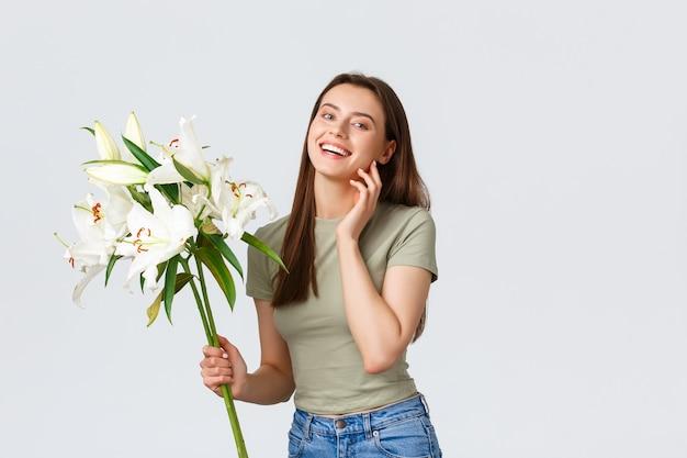 De glimlachende knappe blanke vrouw ontvangt de levering van bloemen van de bloemistwinkel en kijkt gelukkig naar het boeket witte lelies meisje dromerig aanraken van blad