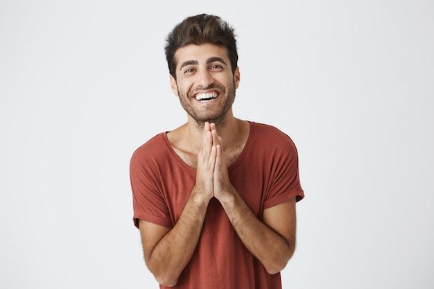 De glimlachende knappe italiaanse ongeschoren palmen van de kerelholding die samen voor hem worden gedrukt die gelukkig over verjaardagsgift van vrouw voelen.