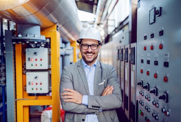 De glimlachende knappe kaukasische zakenman in grijs kostuum en met helm op hoofd die zich met wapens bevinden vouwde naast dashboard. elektriciteitscentrale interieur.