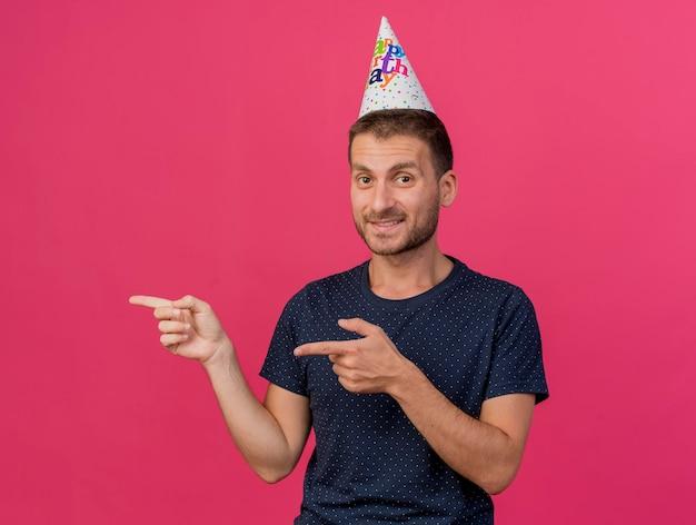De glimlachende knappe mens die verjaardag glb draagt wijst naar kant met twee handen die op roze muur met exemplaarruimte worden geïsoleerd