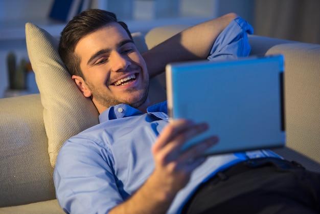 De glimlachende knappe mens gebruikt thuis digitale tablet.