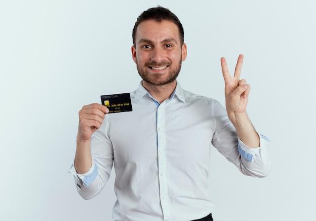 De glimlachende knappe mens houdt creditcard en gebaren twee met hand die op witte muur wordt geïsoleerd