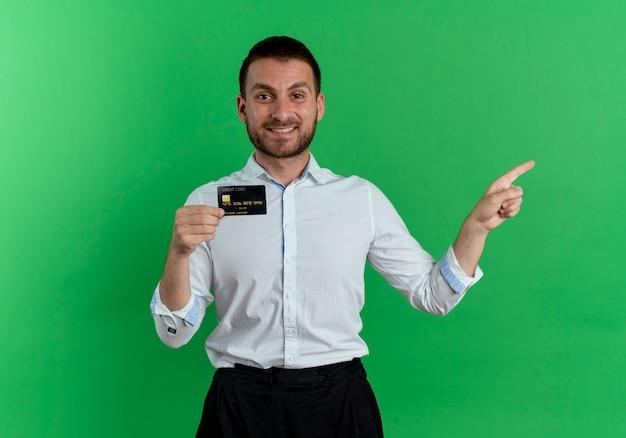 De glimlachende knappe mens houdt creditcard en wijst aan kant die op groene muur wordt geïsoleerd