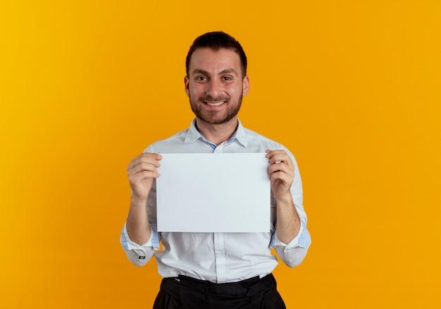 De glimlachende knappe mens houdt document blad dat op oranje muur wordt geïsoleerd