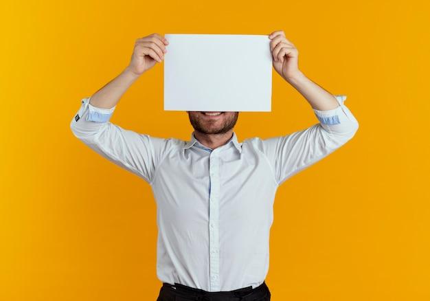 De glimlachende knappe mens houdt en sluit de helft van gezicht met document blad dat op oranje muur wordt geïsoleerd