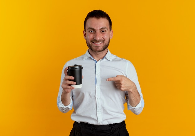 De glimlachende knappe mens houdt en wijst op koffiekop die op oranje muur wordt geïsoleerd