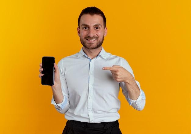 De glimlachende knappe mens houdt en wijst op telefoon die op oranje muur wordt geïsoleerd