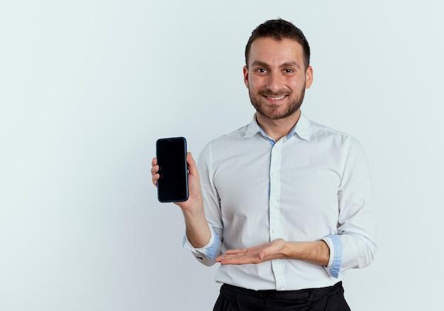 De glimlachende knappe mens houdt en wijst op telefoon met hand die op witte muur wordt geïsoleerd