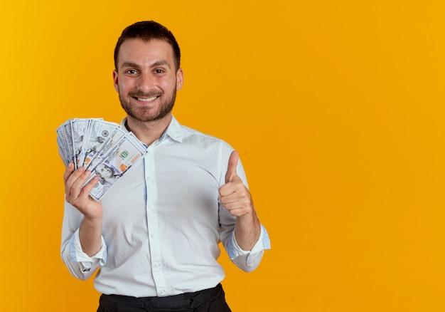 De glimlachende knappe mens houdt geld en duimen omhoog geïsoleerd op oranje muur