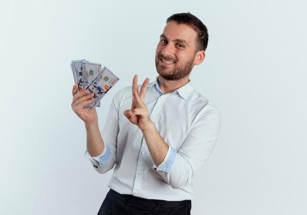 De glimlachende knappe mens houdt geld en gebaren drie met hand die op witte muur wordt geïsoleerd