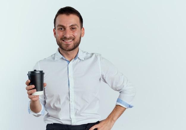 De glimlachende knappe mens houdt koffiekop die op witte muur wordt geïsoleerd