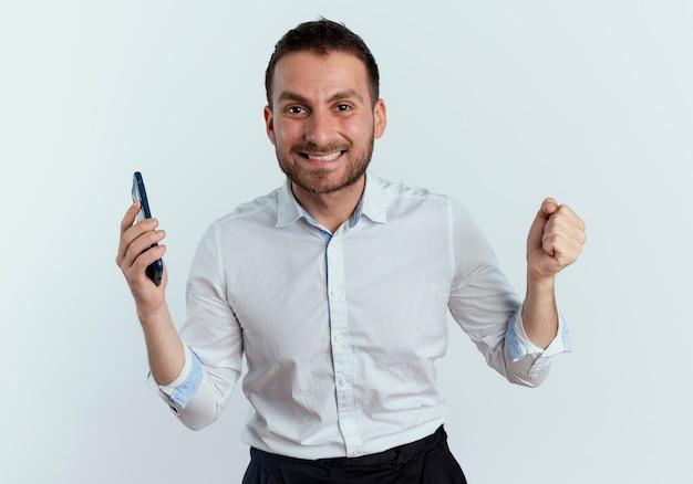 De glimlachende knappe mens houdt telefoon vast en houdt vuist op witte muur wordt geïsoleerd die