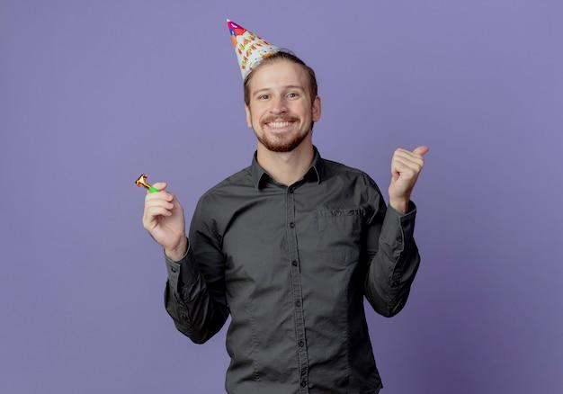 De glimlachende knappe mens in verjaardag glb houdt fluitje en duimen omhoog geïsoleerd op paarse muur