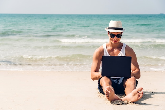 De glimlachende knappe mens ontspant in zonnebril en strohoed die aan laptop op strand werkt