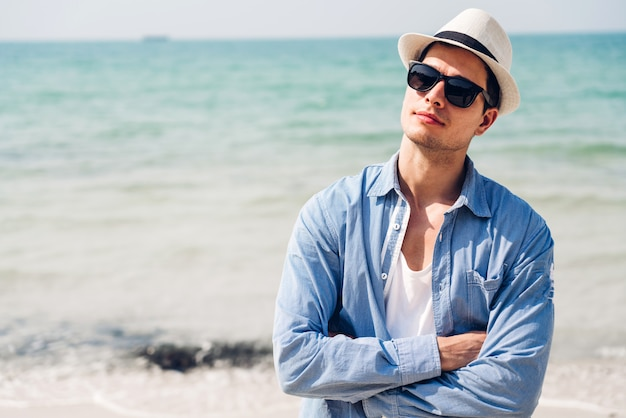 De glimlachende knappe mens ontspant in zonnebril en strohoed op het tropische strand. de zomervakanties