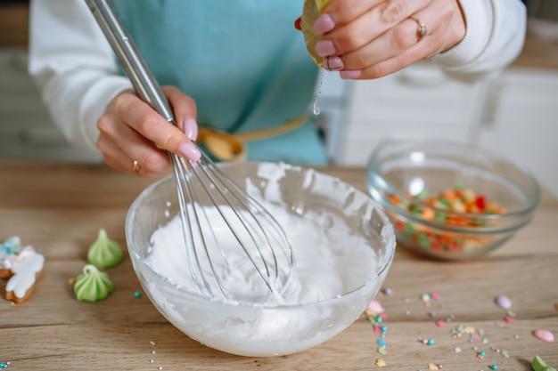 De glimlachende kokkin zwaait met een garde het glazuur voor de paascake op en perst er een citroen in