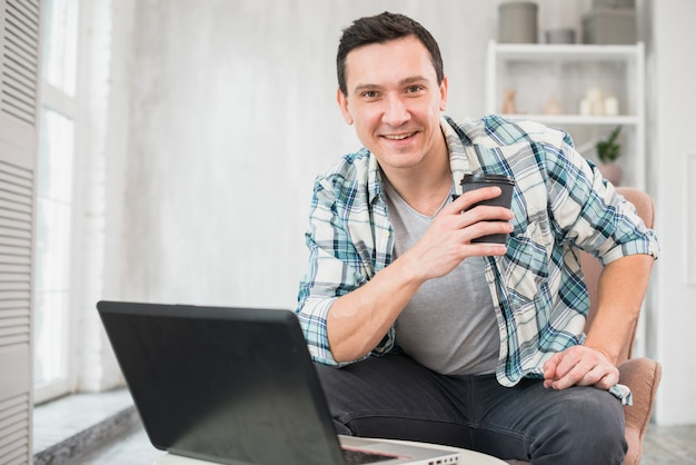 De glimlachende kop van de mensenholding van drank op stoel dichtbij laptop thuis