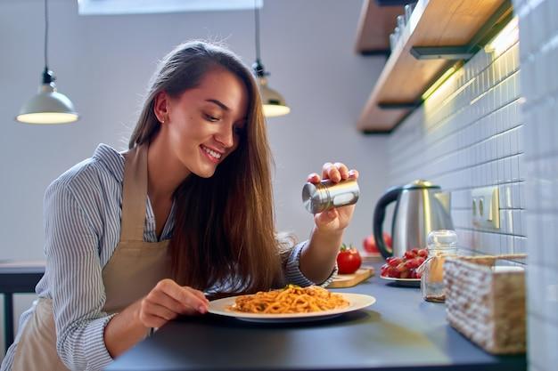 De glimlachende leuke gelukkige jonge kokende vrouwenchef-kok bereidt en zout voedsel voor diner voor