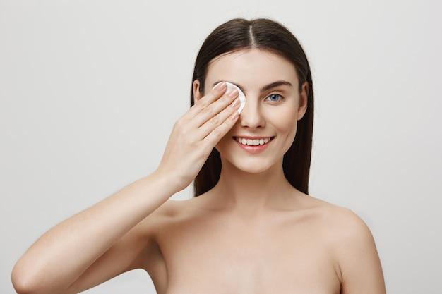 De glimlachende leuke make-up van de vrouwenstart met wattenschijfje