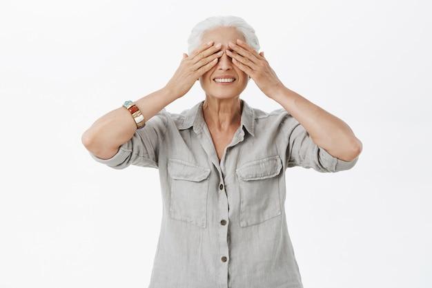 De glimlachende leuke oude dame sloot ogen met handen en wachtend op verrassing