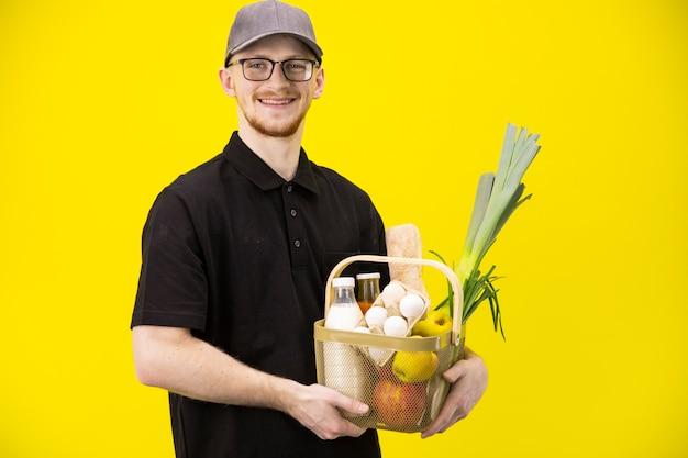 De glimlachende leveringsmens houdt mand met biologische landbouwproducten, online levering