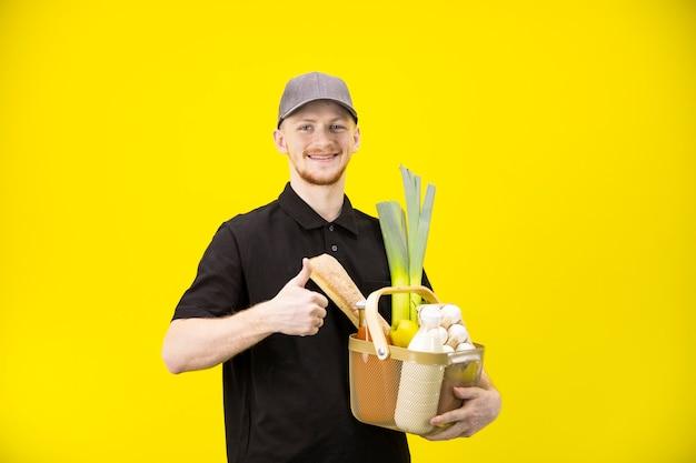 De glimlachende leveringsmens houdt mand met kruidenierswaren die als teken met omhoog duim tonen