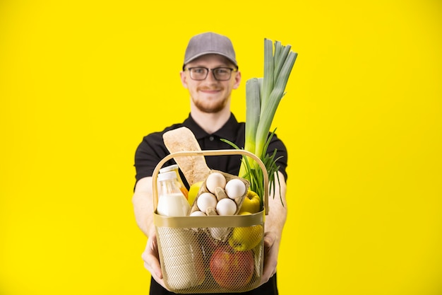 De glimlachende leveringsmens houdt mand met kruidenierswaren, nadruk op mand