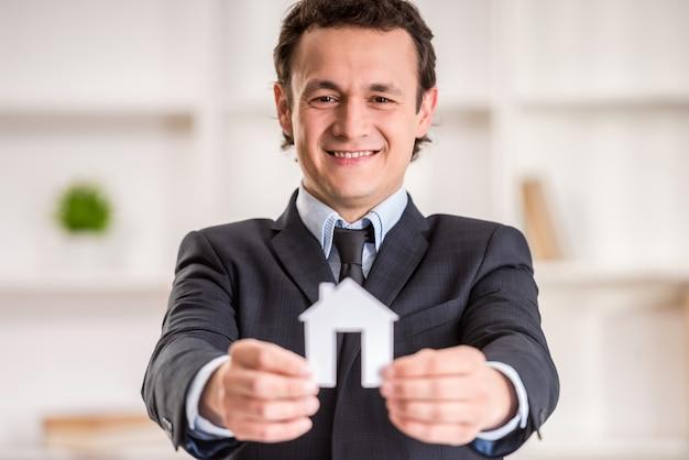 De glimlachende makelaar in onroerend goedmens houdt een model van huis.
