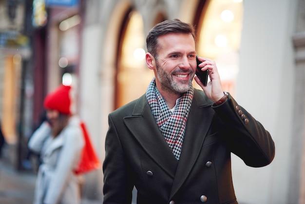 De glimlachende man is aan de telefoon